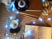 Christmas background with candles, cones, garland. Christmas background with candles, cones, books and blue glowing lights stock image
