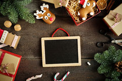 Christmas background with chalkboard, candy cane, decorations, gift boxes, ribbon and ginger bread on wooden board. Royalty Free Stock Photos