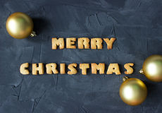Christmas background with Christmas balls and baked gingerbread words merry christmas . creative idea Royalty Free Stock Photography