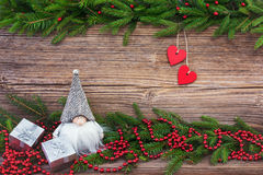 Christmas background. Christmas fir tree with red hearts and decoration on old wooden  background. Toned Stock Images