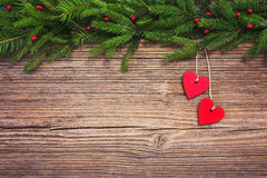 Christmas background. Christmas fir tree with red hearts on old wooden board background, copy space. Toned Royalty Free Stock Images