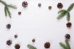 Christmas background. Christmas frame made fir tree branches, and pine cones decoration rustic elements on white trable. stock photography