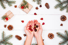 Christmas background with Christmas gift, fir branches, pine cones, red decorations. Female hands.Flat lay, top view Royalty Free Stock Photo