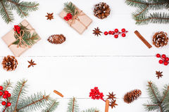 Christmas background with Christmas gift, fir branches, pine cones, snowflakes, red decorations.  Flat lay, top view Royalty Free Stock Image