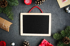 Christmas background with christmas presents, decoration, balls, candles, postcard and empty chalkboard on grey background. Overhead view royalty free stock photos