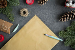 Christmas background with christmas presents, decoration, postcard and empty Christmas letter to Santa on grey wall. Stock Images