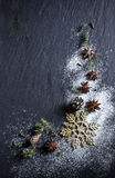 Christmas background. Christmas stars and spices on black stone background Royalty Free Stock Image