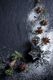 Christmas background. Christmas stars and spices on black stone background Stock Photography