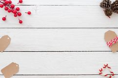 Christmas background with christmas tags, holly berry, pine cons and candy cane on white wooden background. Creative Flat layout and top view design Royalty Free Stock Image