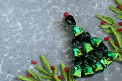 Christmas background with Christmas tree of chocolates and candi. Festive background with Christmas tree of chocolates in shiny green candy wrappers and candied Stock Photography