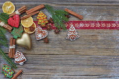 Christmas background. Christmas tree, homemade gingerbread cookies, golden heart, cinnamon sticks on old wooden background. Copy s Royalty Free Stock Images