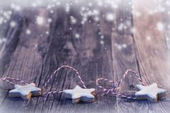 Christmas background with cinnamon star and snow. Wooden background with cinnamon star and snow stock images