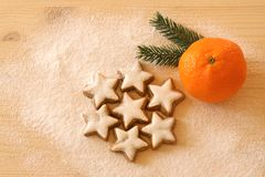 Christmas background with cinnamon stars and a tangerine and a pine branch on wood royalty free stock photography