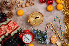 Christmas background with a clock and a golden piggy bank, sweets, Christmas balls and tangerines. stock photos