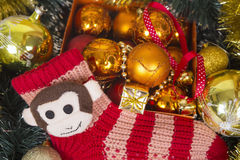 Christmas background with colored balls and monkey on red sock. Stock Photos