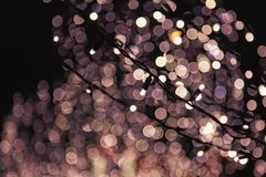 Christmas background of colored glowing bokeh. Garlands illuminated decoration of lights on the Xmas tree. Tinted photo Royalty Free Stock Image