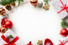 Christmas gift box with red ball and pine cones on white background. royalty free stock image