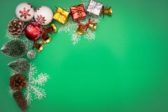 Christmas background concept. Christmas gift box and tree with golden bells, pine cones, red and white ball on green background royalty free stock photos
