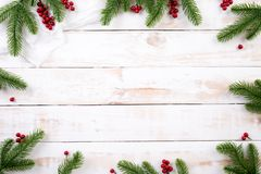 Christmas background concept. Top view of Christmas green and red gift box with spruce branches, pine cones. Red berries and bell on white wooden background stock photos
