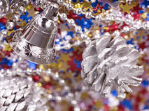 Christmas background with cone, bell and confetti. Royalty Free Stock Photo