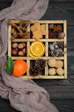 Christmas background with Cones, Gingerbread Cookies, Nuts, Spices and Dried oranges. Royalty Free Stock Image