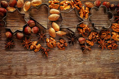 Christmas background with cookie cutters, nuts and anisetree. On a dark wood background. tinting. selective focus Stock Photography