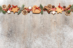 Christmas background. With cookies, fir branches and spices on the old grunge wooden board Stock Photos