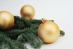Christmas Background with Copy Space. Golden Cristmas Tree globes or Balls with Fir Branches Isoalted. Festive Greeting card. Royalty Free Stock Images