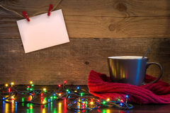 Christmas background with cup wrapped in red scarf and lights on Stock Photo