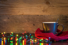 Christmas background with cup wrapped in red scarf and lights on. Wood texture with place for text Stock Photography