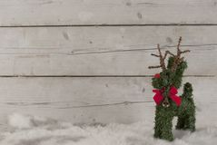 Christmas background, cute reindeer standing on sheepskin, Royalty Free Stock Images