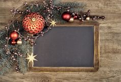 Blackboard with text space and Christmas decorations on black ba Stock Photos