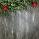 Christmas background with decorated pinetree. Christmas background with glowing colorful balls and green pine tree on old wooden board Stock Images