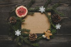 Christmas background. Christmas decoration with fir branches and gingerbread man cookie on the wooden table. Stock Photo