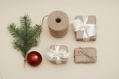 Christmas Background with Christmas Decoration, Red Ball, gift boxes wrappeed in Craft Rustic Paper, Fir branch, top view stock image
