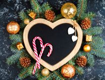 christmas background - decorations and fir branch on a table, a frame in the shape of a heart, top view, place for text, flat lay, royalty free stock photo