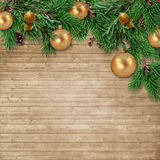 Christmas background with decorations and firtree on wooden boar. Christmas card. a border of green fir branches with balls and pine cones on a wooden background Stock Photo