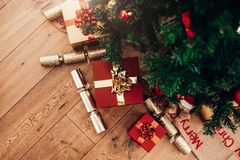 Gift boxes and Christmas crackers placed beside Christmas tree. Stock Photo