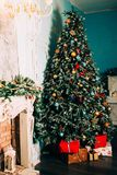 Christmas decoration in grunge room interior with fireplace, horse rocking kids chair, classic new year tree with presents Royalty Free Stock Images