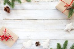 Christmas background with decorations and handmade gift boxes on white wooden board. stock photo
