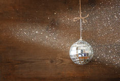 Christmas background with decorations hanging on a rope over wooden background. glitter overlay. Stock Photos