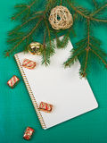Christmas background. Christmas decorations and notebook on a green background Stock Photos