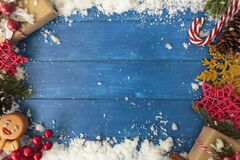 Christmas background with decorations and presents on blue wooden table. Top view with copy space