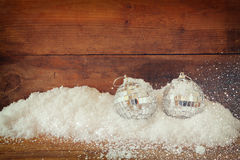 Christmas background with decorations on snow over wooden background. glitter overlay. Royalty Free Stock Photography