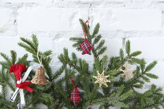 Christmas background with decorative elements. Spruce branches with decorative ornaments on the background of a white brick wall royalty free stock image