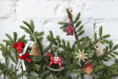 Christmas background with decorative elements. Spruce branches with decorative ornaments on the background of a white brick wall stock photos