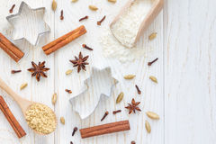 Christmas background with different spices, flour and cookie cutters on white wooden table, copy space, top view Royalty Free Stock Image