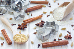 Christmas background with different spices, flour and cookie cutters on white wooden table Royalty Free Stock Image