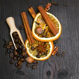 Christmas background: dried orange, coffee beans, cinamon, anise and cloves. On dark brown wooden plank, copy space Royalty Free Stock Photos