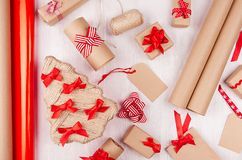 Christmas background - eco handmade gift boxes of kraft paper, tree, labels, roll wrapping paper, red bows and ribbons on white. Wood table, pattern stock photos